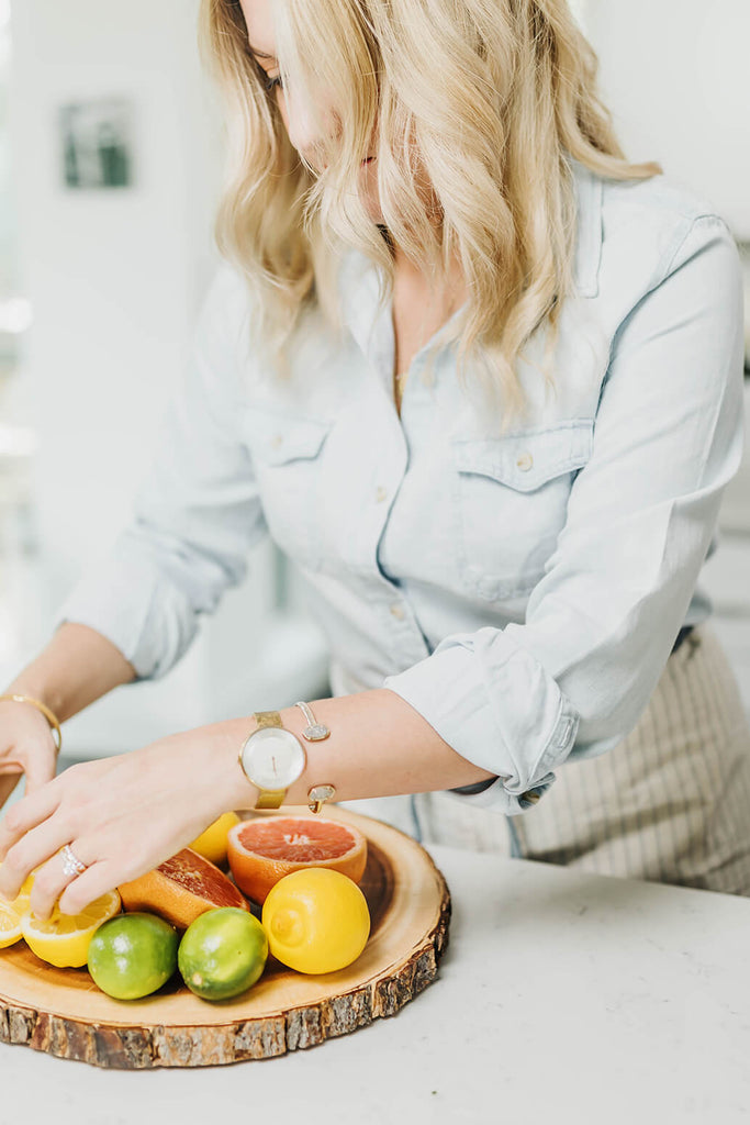 blonde woman arranging citrus on a cutting board