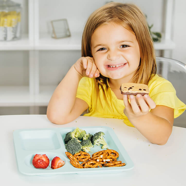 child with protein bar and healthy snacks