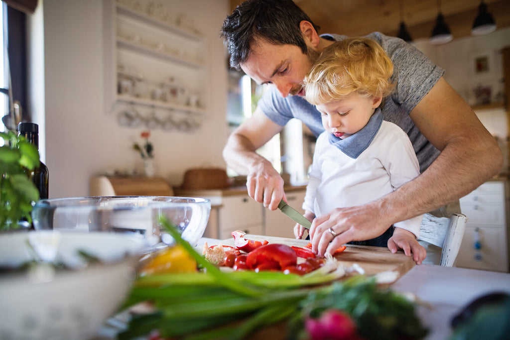 father helping toddler make healthy meal