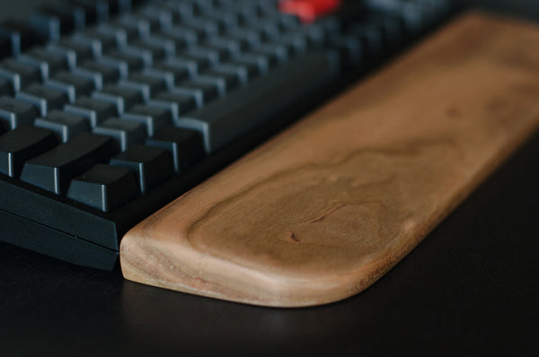 A wooden keyboard wrist rest from the side