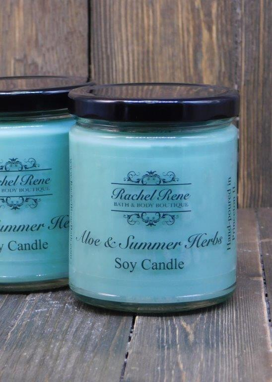 Teal candle in a stout glass jar with black lids labeled Aloe & Summer Herbs.