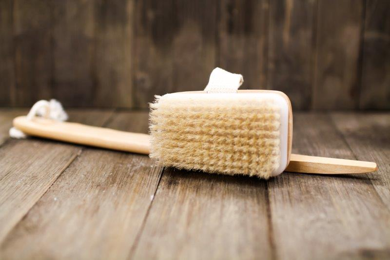 A long wooden body brush with a detachable head. The head has a canvas band.