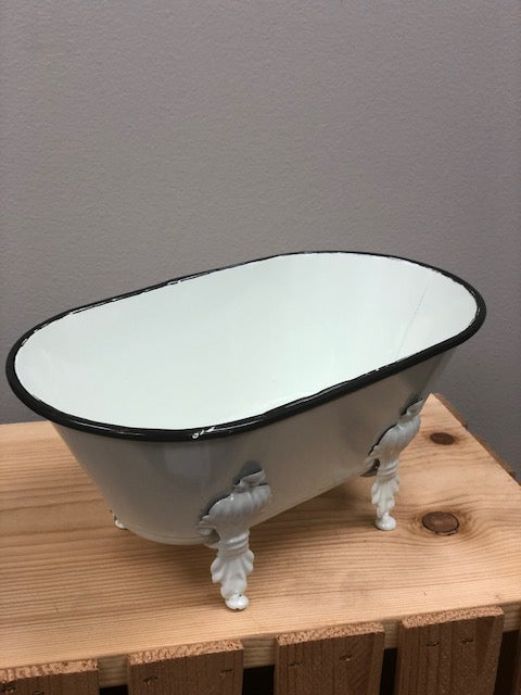A medium white decorative bathtub to hold products with detailed footing and black trim on the top.