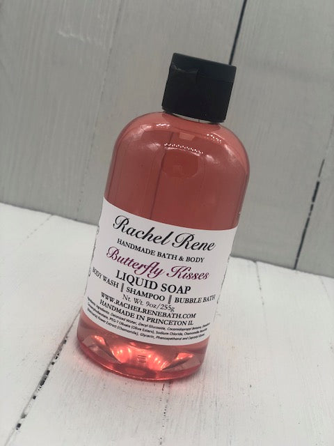 "Pink semi-transparent liquid soap in a clear bottle with a black lid labeled ""Butterfly Kisses"""