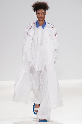 Catwalk image from CIMONE SS17 featuring model Vanessa David. Colourful embroidered paint splashes on crisp white cotton 'Helios' trench coat from emerging brand CIMONE. Embellishments and overall look at echoed by Oscar de la Renta one year later in SS18 - be ahead of the trends and support new brands!