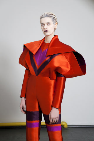 "Channel the original David Bowie 'Starman' with this statement all-in-one. Featuring an oversized 'winged' shape extending down from the shoulder. A sister to the ""Boeing"" dress, this piece is draped with a wrap at the shoulder point. The fitted body and slim line leg further accentuates the scale of the outstretched wing."