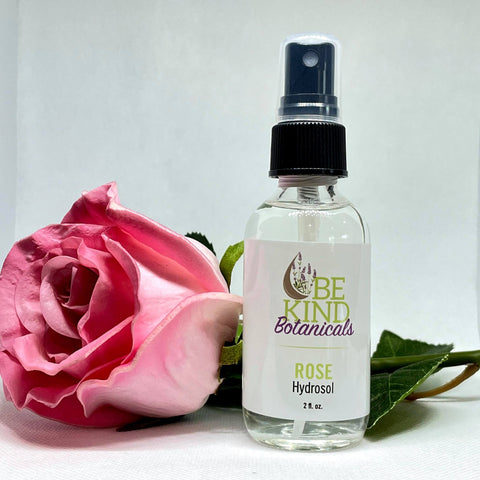 "A Pink rose behind a spray bottle with label reading ""Rose Hydrosol"" from Be Kind Botanicals"