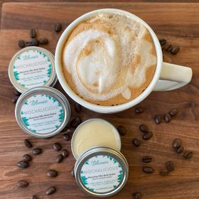 Three tins of Mochalicious body butter with a cup of frothy coffee and coffee beans scattered on a table
