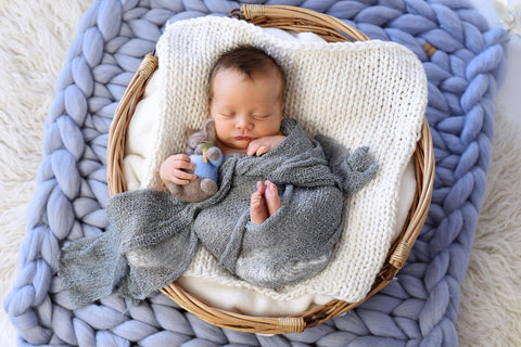 Newborn baby posed in a basket on top of a chunky knit blanket