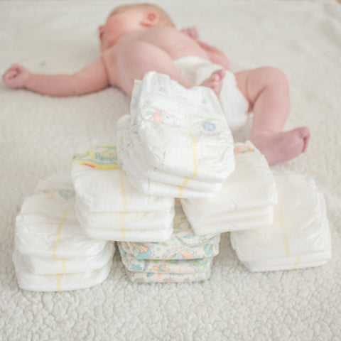 Diaper samples stacked in front of baby