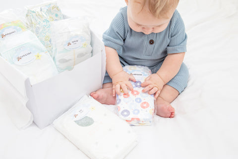 sitting baby holding a Diaper Sample Pack with a box full of Diaper Sample Packs next to him