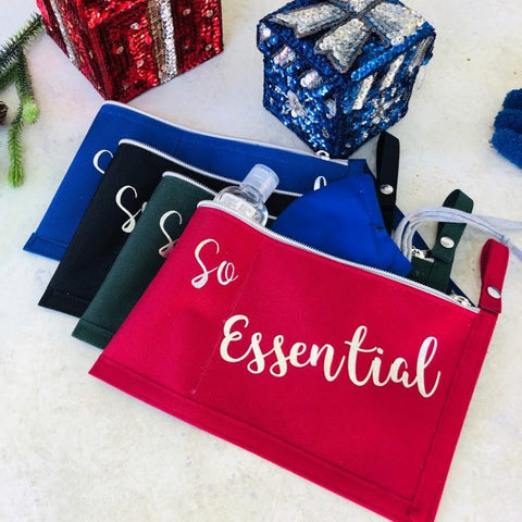 "Set of 3 zippered pouches in blue, black and red with ""so essential"" printed on the bags. Background of gift wrapped boxes in blue and red"