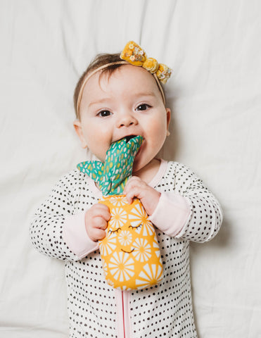 Baby chewing on a pineapple shaped rattle