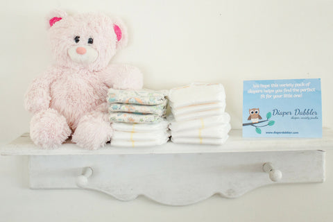 Multiple brands of diapers on a shelf with teddy bear