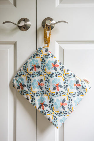 Wetbag hanging from silver doorknob on a white door