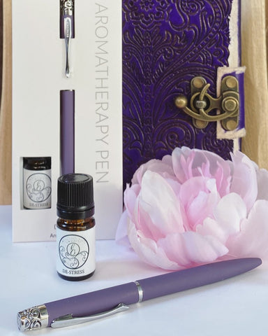 Photo of Essential Oil pen and bottle of essential oil with a lavender flower and in the background a gift boxed set of same pen with essential oil bottle