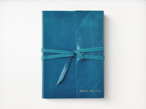 """Photo of teal journal with wrap with silver embossing in lower right corner """"positive vibes only"""""""