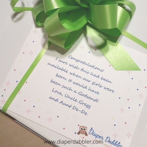 White gift box with green ribbon and a gift card