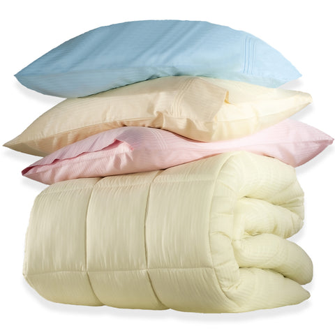 folded down comforter on which is a pile of pillows: pink, pale yellow and blue