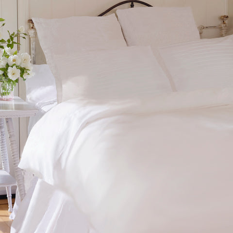 Romantic looking wrought-iron bed with white duvet cover, bed skirt and pillows & flowers on bedside table