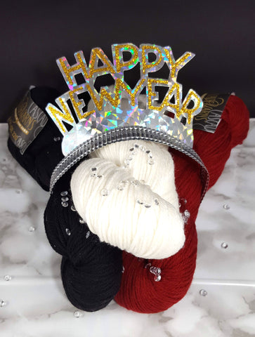 a red, white, and black skein of yarn topped with a new year tiara and a sprinkling of rhinestones