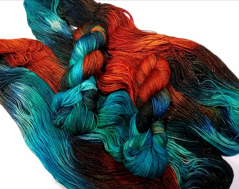 Gorgeous intensely dyed yarn. Orangey reds, teal and brown black on a sparkly base