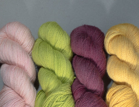 four skeins of yarn laid in a row.  pink, chartreuse, burgundy, yellow