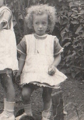 Image of a little curly haired girl in a dress and pinafore with bare legs, socks and shoes on.  Taken circa 1928.