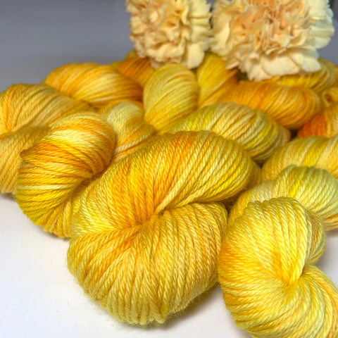 four skeins of yellow tonal yarn topped with yellow chrysanthemums