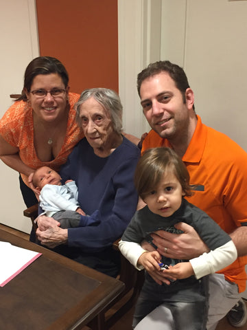 An old woman, Iris, surrounded by the young family of her granddaughter Marisa, her husband Andrew, and their children.