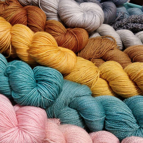 Skeins of yarn lay on a diagonal in colours pink, teal, yellow, copper, light grey, dark grey