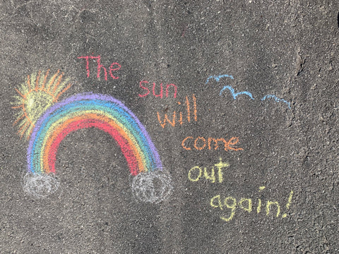 chalk rainbow drawn on dark grey asphalt with words The sun will come out again!