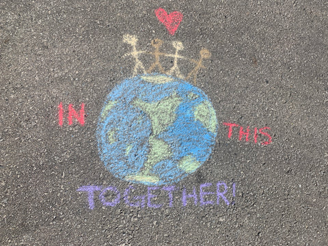 "Chalk Drawing of the earth with people holding hands on top with the words ""In this together"""