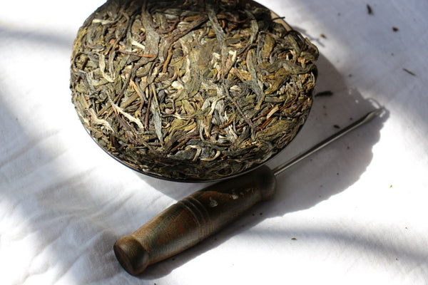 dry leaves compressed pu-erh tea and knife