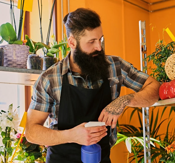 man with big beard watering the plants