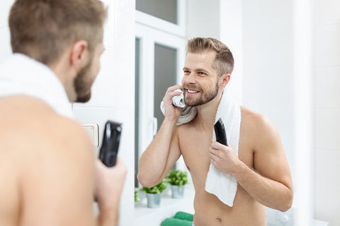 man trimming his patchy beard