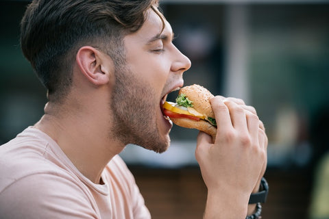 man with a patchy beard eating a junk food
