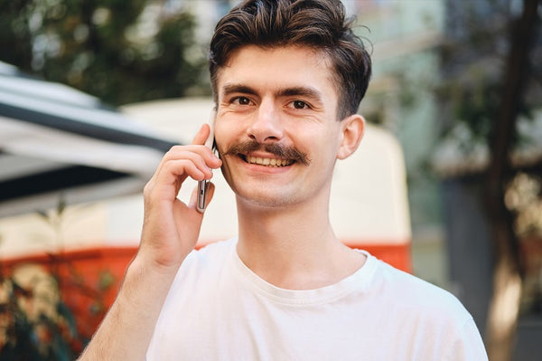 man with moustache talking on the phone