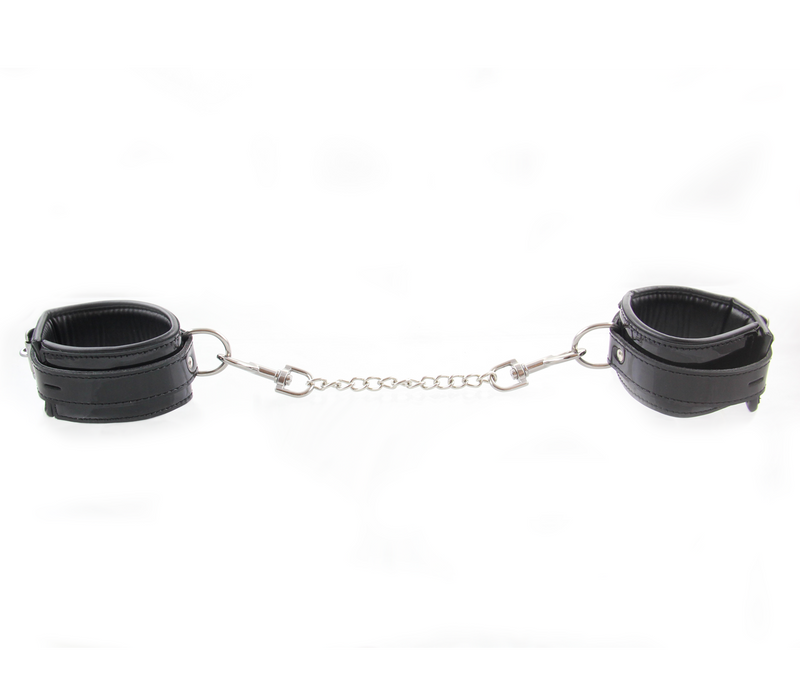 Patent leather wrist restraints with chain join and lockable buckle.