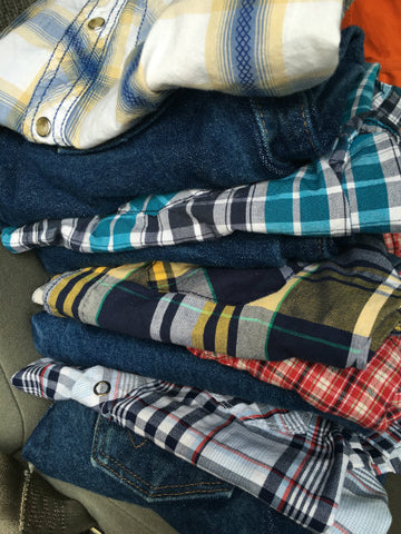 Pile of folded jeans and button-down shirts