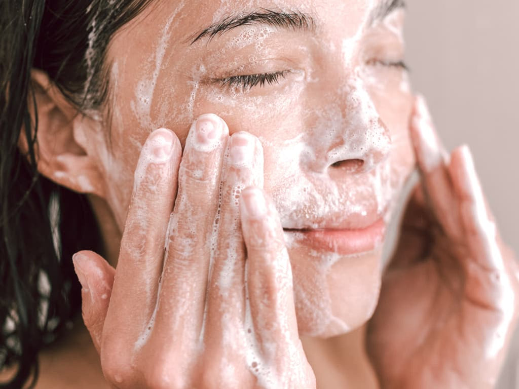 Woman washing face with goat milk soap in shower