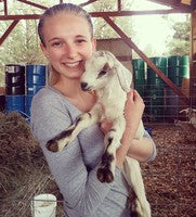 Julia holding a baby goat on the farm