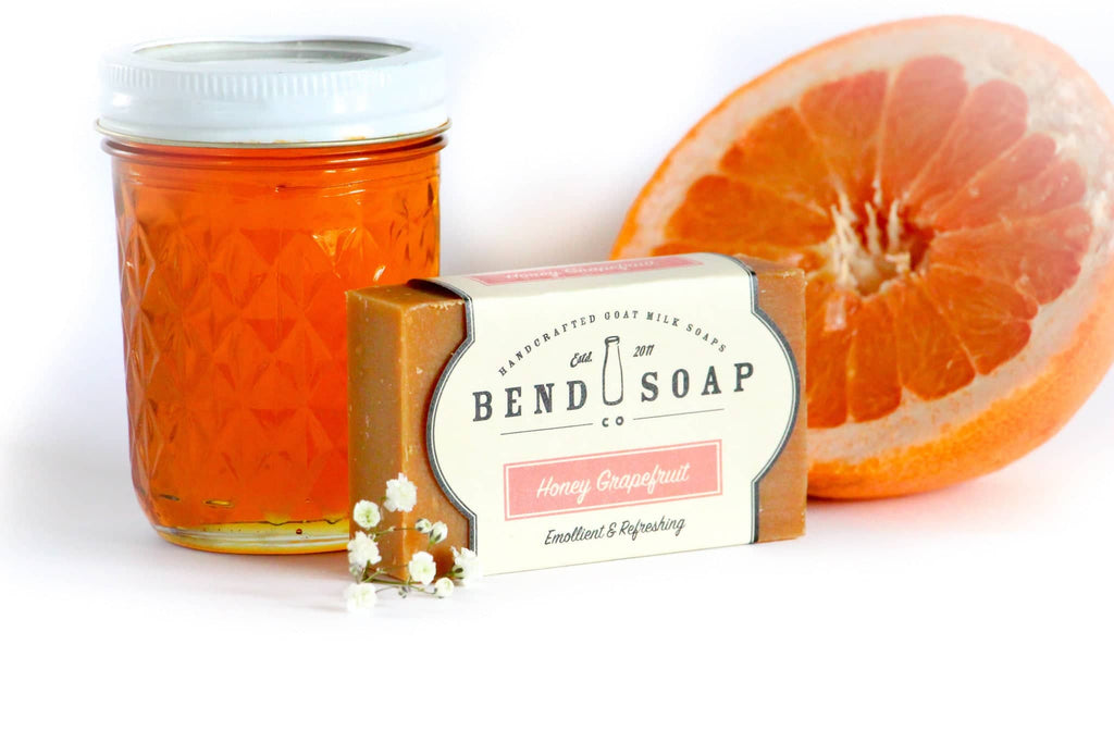 Full Size Honey Grapefruit bar of soap wrapped in Honey Grapefruit label next to Honey, Grapefruit and Ylang Ylang