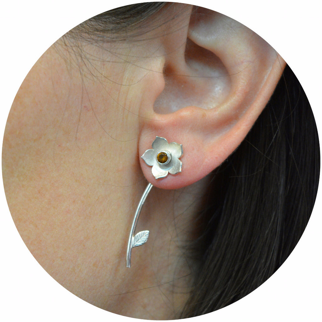 Flower gem-set stud earring set in sterling silver on ear