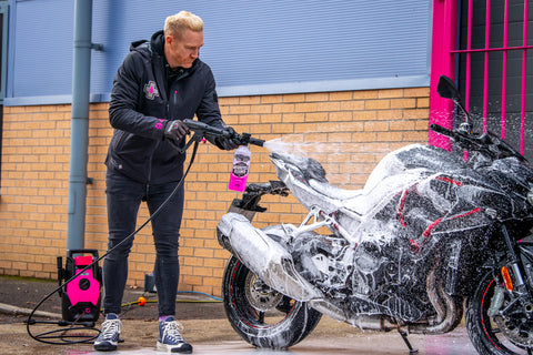 Iwan Thomas cleaning a motorcycle with a pressure washer