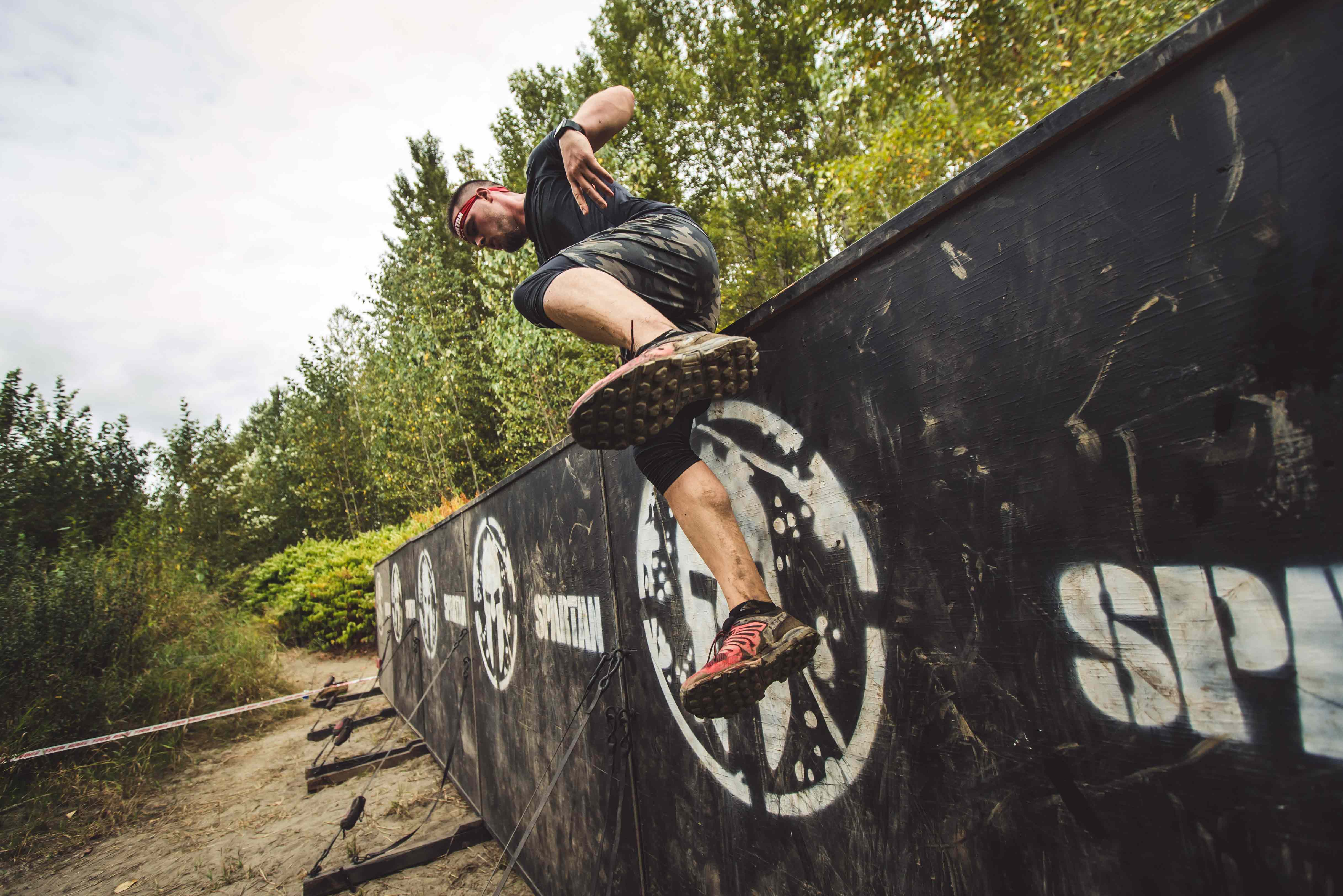A Spartan racer clears an obstacle wall during a race safely after preparing with ankle stability exercises.