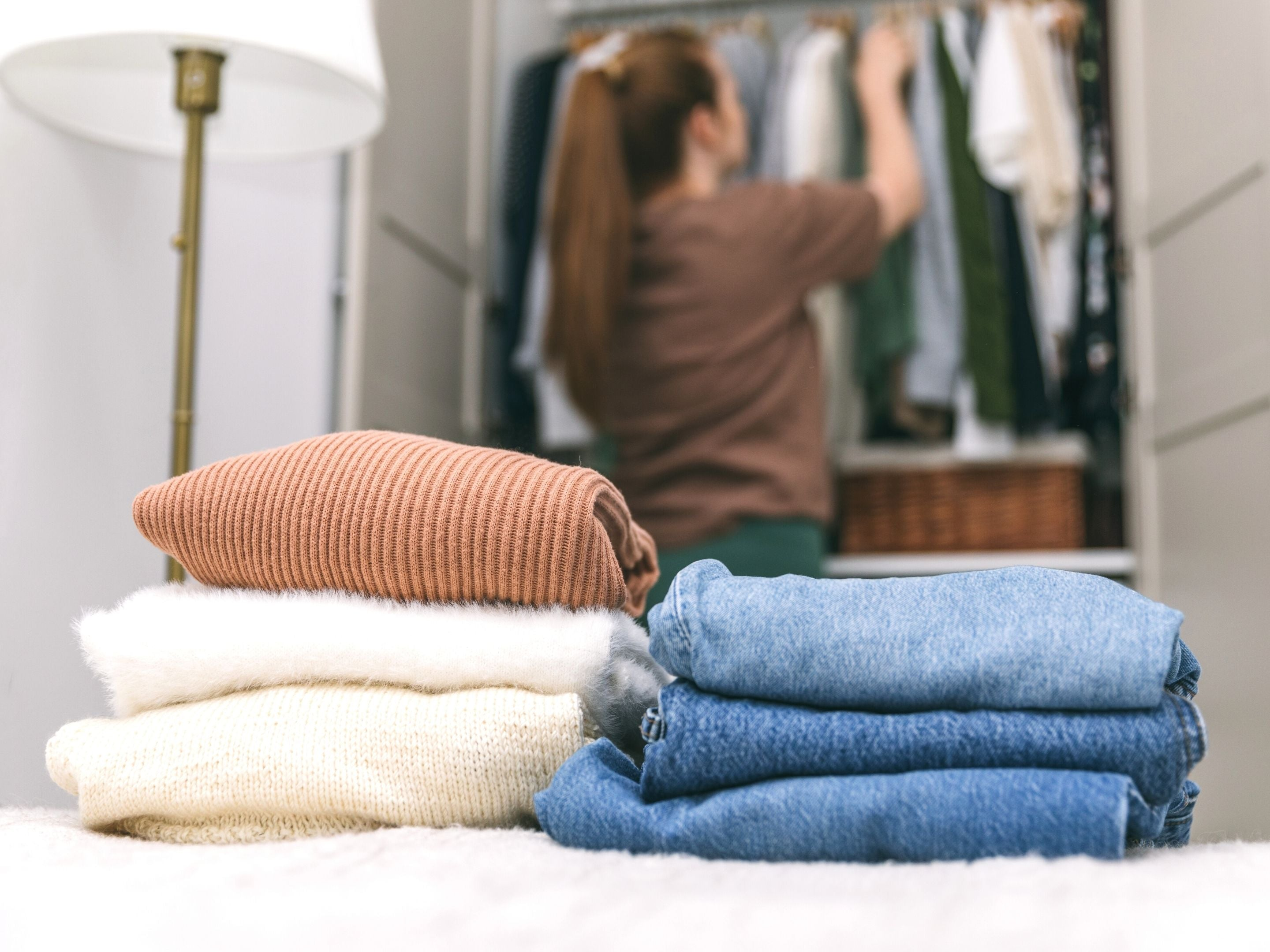 Folded Garments and Woman Hanging Clothes in Closet