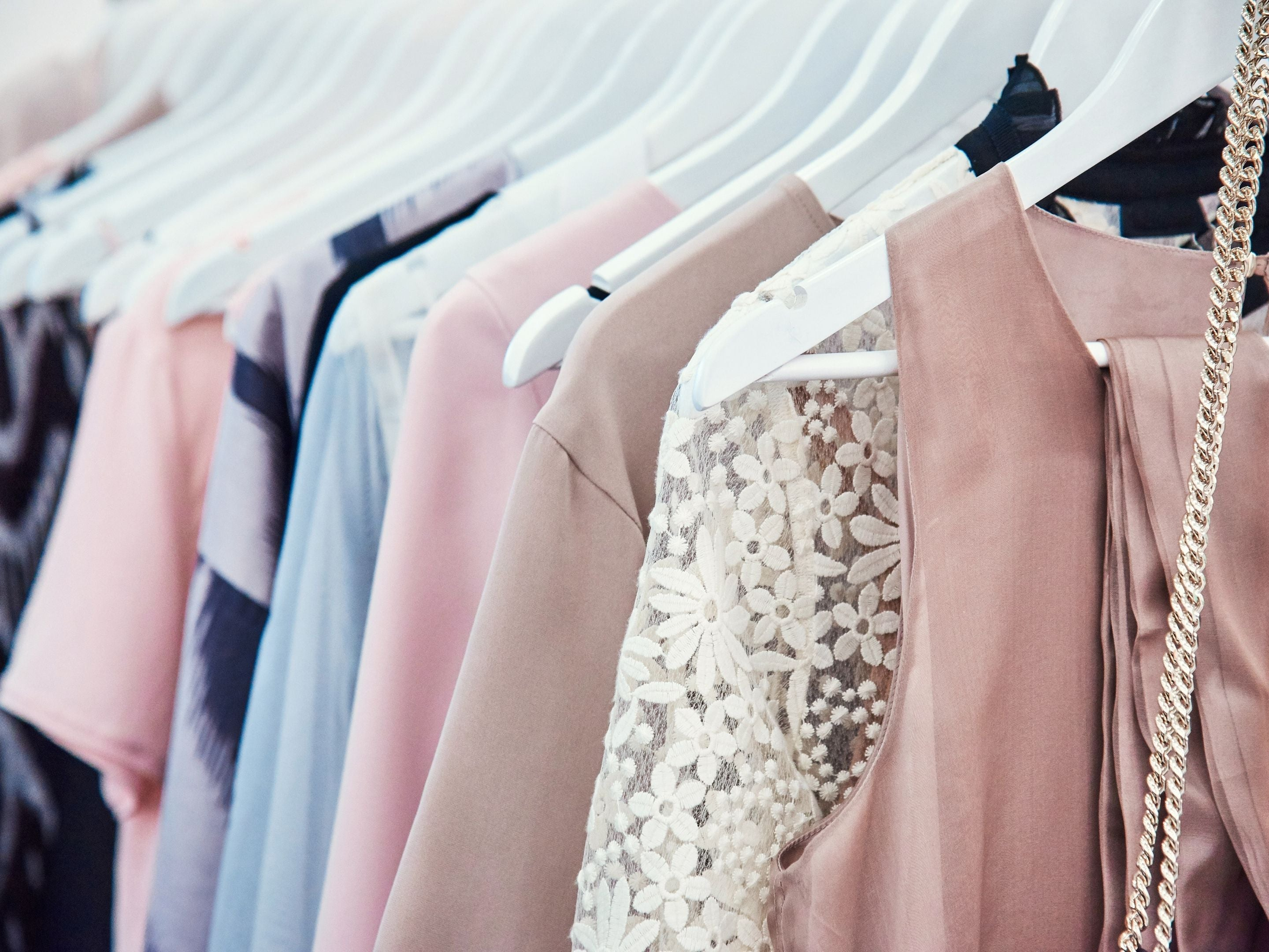 Assorted Garments Hanging in a Closet on Hangers