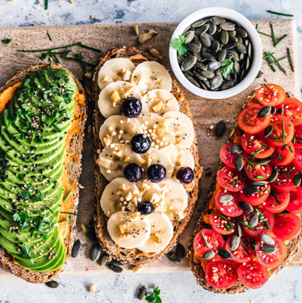 A vegan meal made up of avocado, bananas, berries and tomatoes.