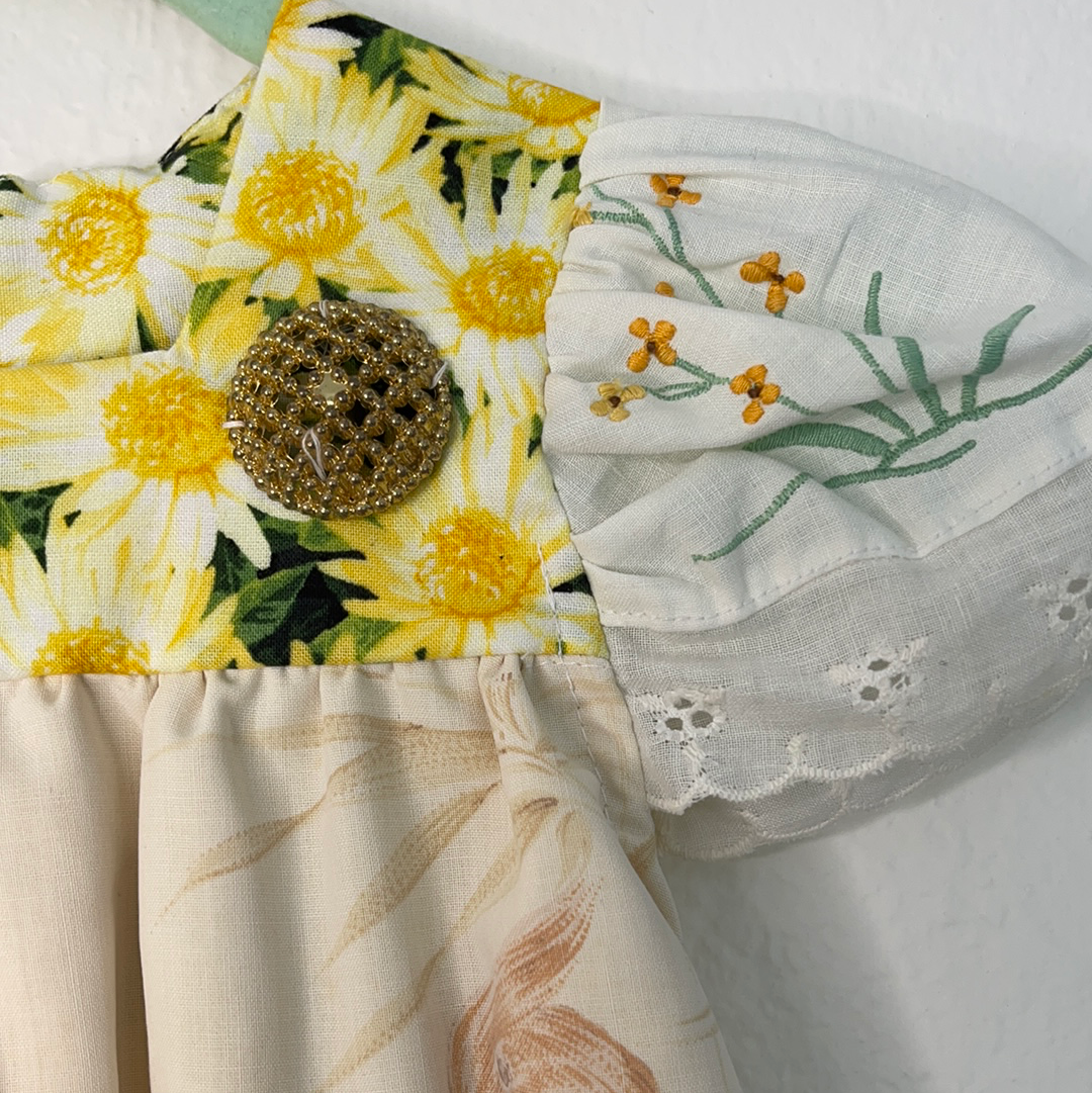 Left shoulder of Baby's Vintage yellow and white floral tunic